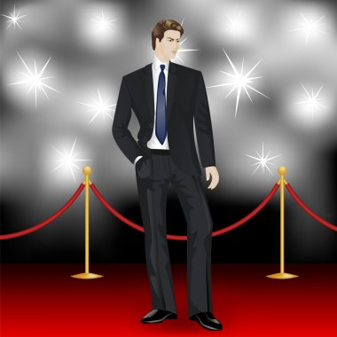 Man in suit posing in front of the paparazzi on the red carpet