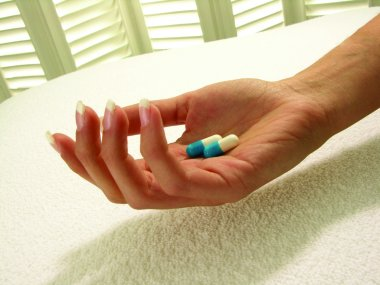 Hand with a two medical pills