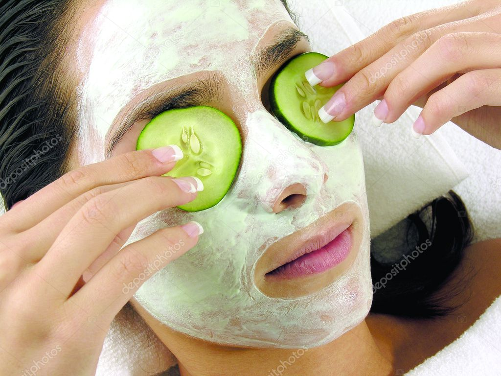Young girl with facial mask of cucumber