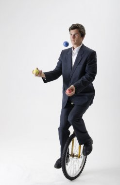 Juggling businessman on unicycle