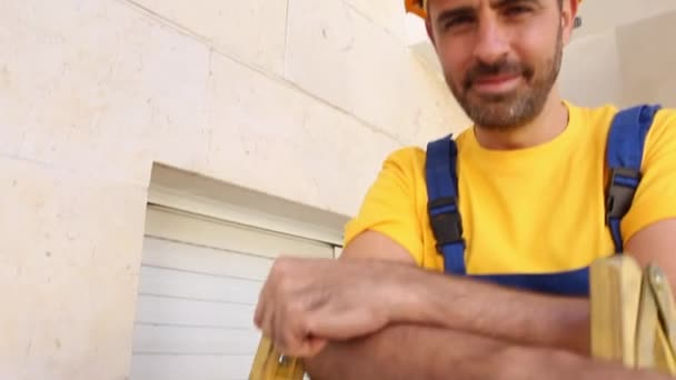 Builder with worker cloths stand on a ladder