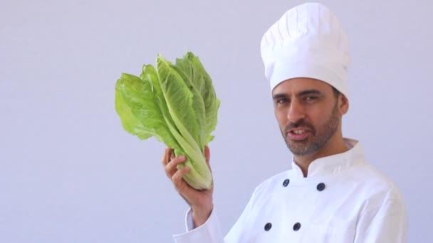 kuchařka či kuchař drží čerstvý hlávkový salát