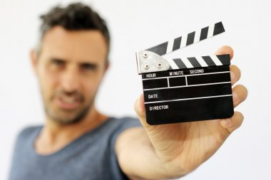 Young man holding movie clapper