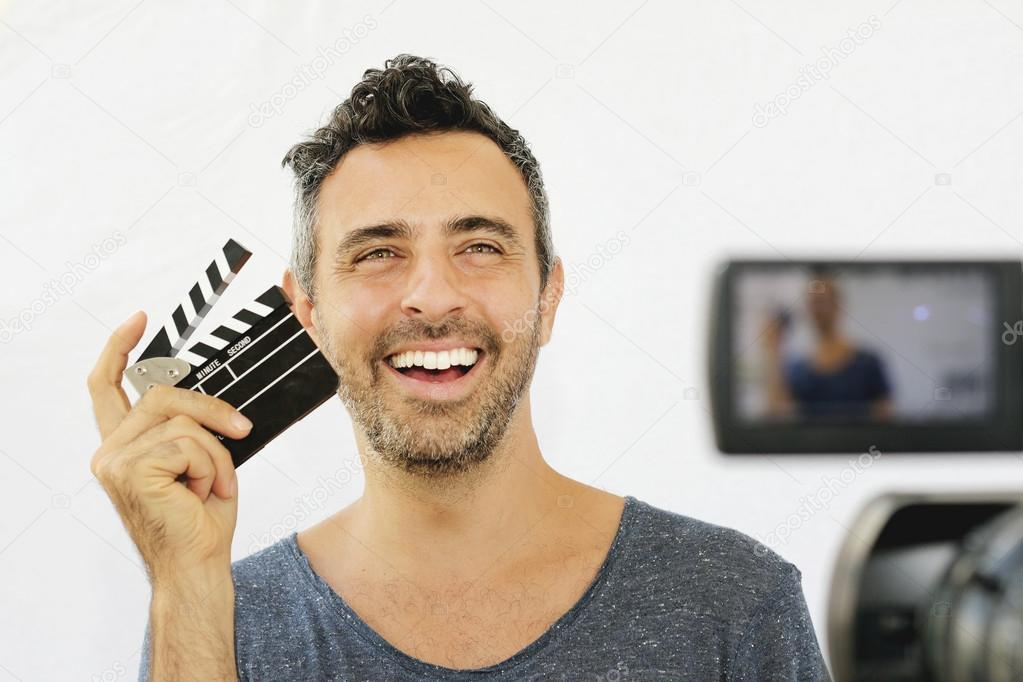 Young guy holding film clapper