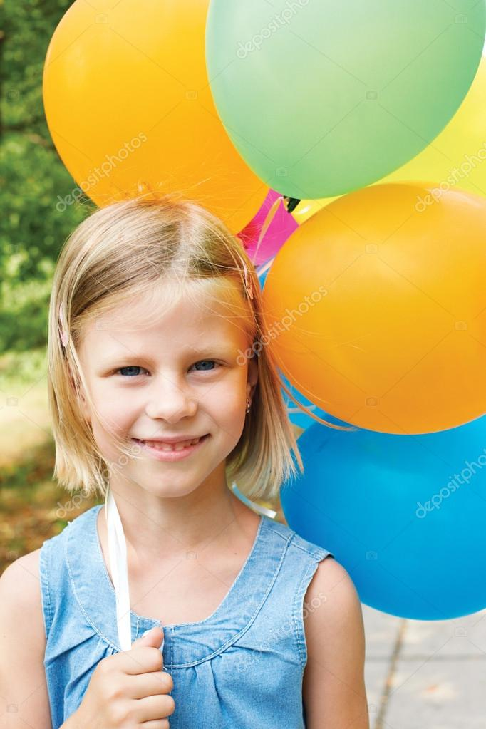 smiling girl with balloons on the street in the summer