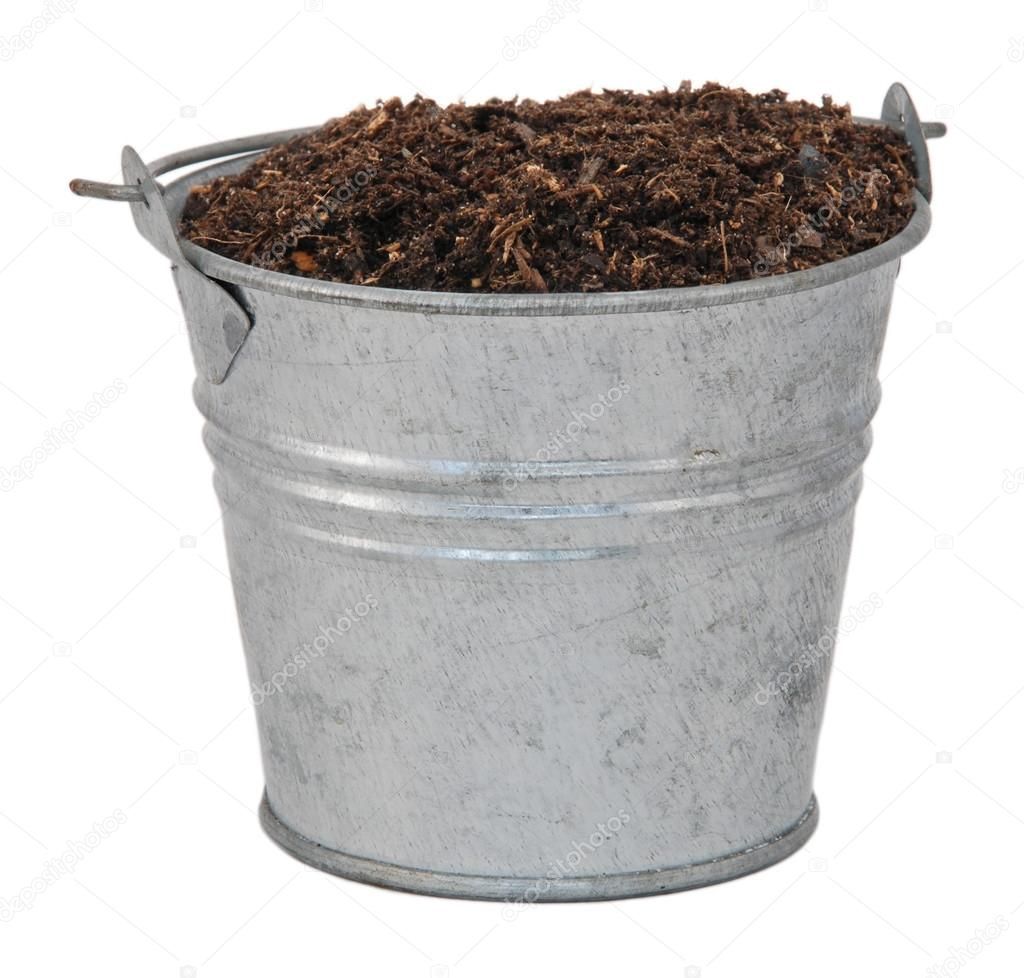 Compost, soil or dirt in a miniature metal bucket