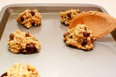 Spooning oatmeal raisin cookie dough onto a baking sheet