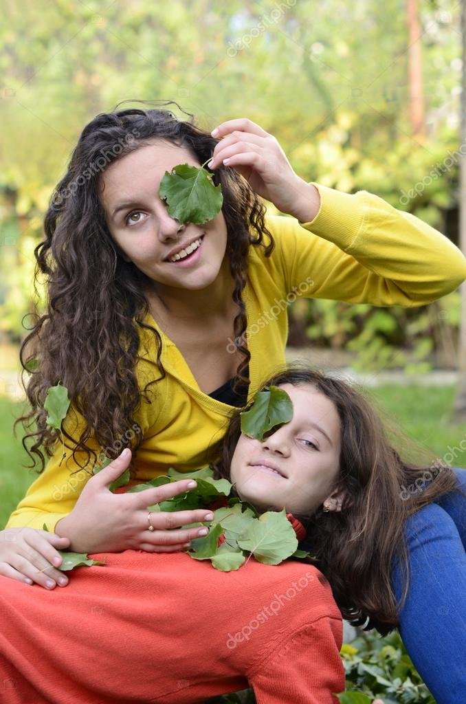 Two beautiful teenager having fun playing in the garden with green leafs on their eyes