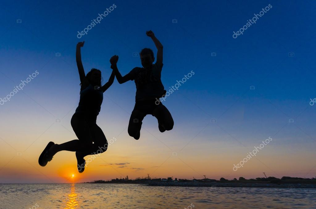 Silhouette of Girl and boy jumping on the beach sunset