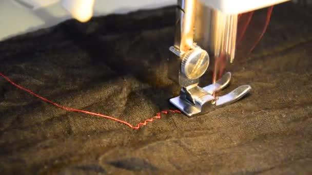 šicí stroj a kus černého oblečení, kontrastní červenou nití