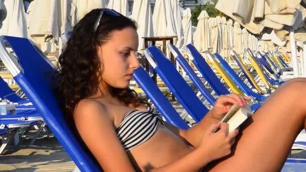 Girl Sunbathing  reading book at the beach