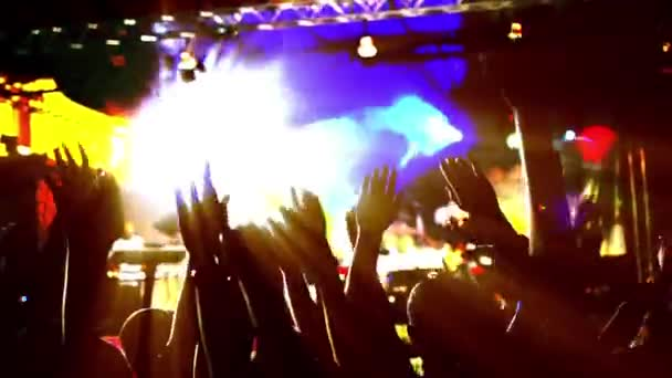 People hands up silhouette backlit and colorful lights on concert