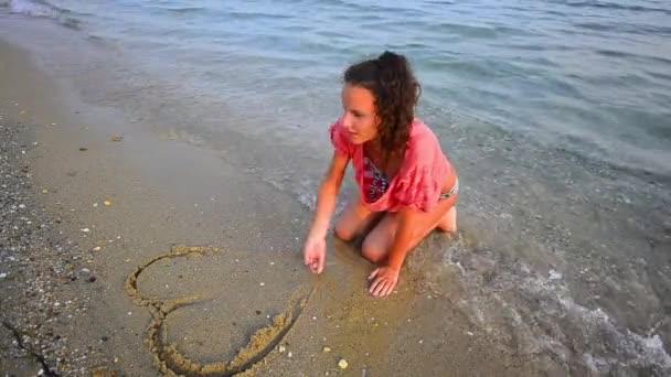 dívka na pláži, nakreslit srdce odstraněna po moři