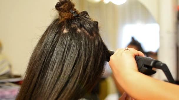 Dívka dělá kadeřní žehlička na vlasy