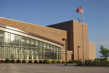 Modern high school with American and Minnesota flags flying