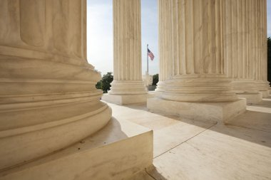 American flag viewed between columns of Supreme Court building
