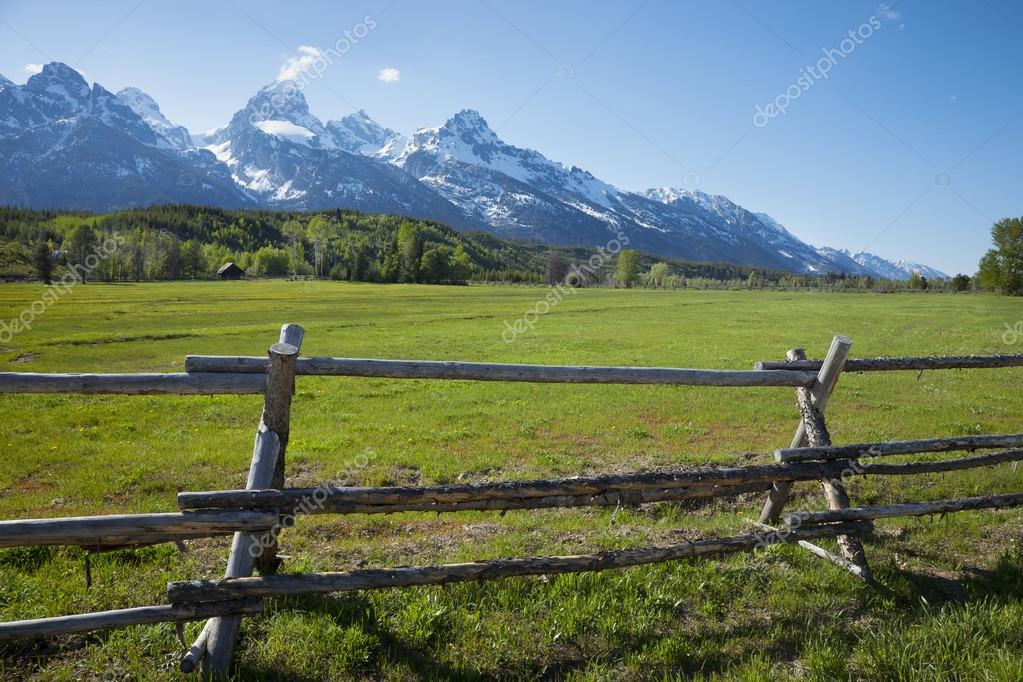 Horse ranch field and fence below grand teton mountains of for Grand ranch
