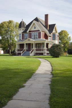 Victorian house with lawn and sidewalk on sunny afternoon