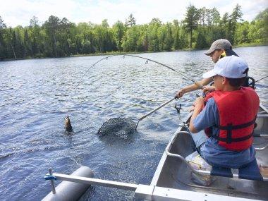 Boys fishing in a canoe catch a walleye