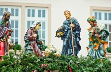 Christmas nativity scene with three Wise Men presenting gifts to baby Jesus, Mary & Joseph.