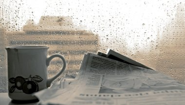 Cup of coffee,-newspaper and rain outside window