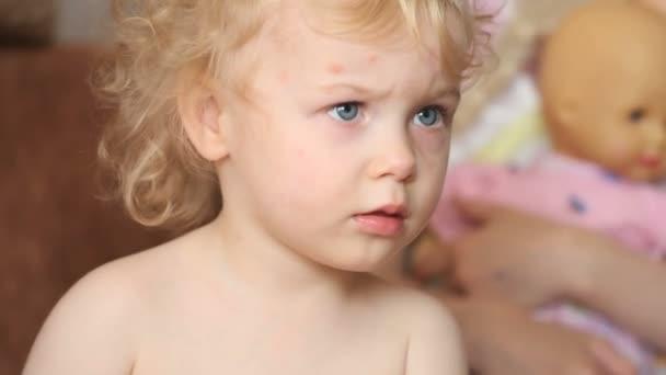 ernsthafte zwei Jahre alte lockige Haare Baby Mädchen fernsehen zu Hause