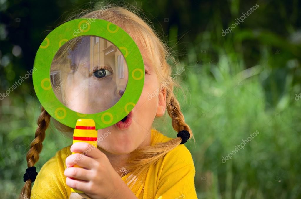 Girl with surprise looks through a magnifying glass