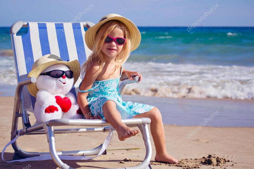 A child sits on a deck chair with a toy