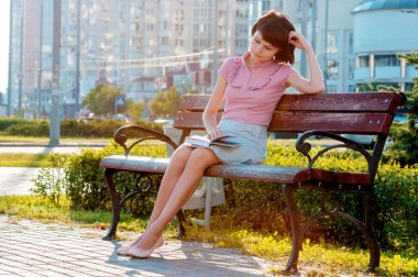 beautiful brunette woman sitting on a bench in a park and reading a book