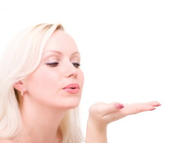 Blonde woman blowing while sending an air kiss
