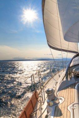 Yacht sailing towards sunset on blue sea