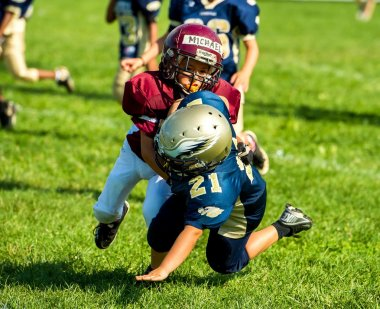 Youth football player tackles another