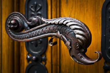 Decorative antique door handles with fish pattern on a big chatedral