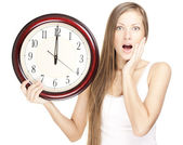 Překvapený atraktivní mladá žena drží velké hodiny, izolovaných na bílém pozadí