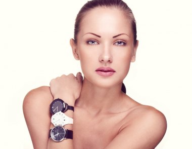 Close-up portrait of a beautiful woman with watches in fashion makeup