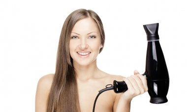 Smiling beautiful woman drying her beautiful long hair with hairdryer