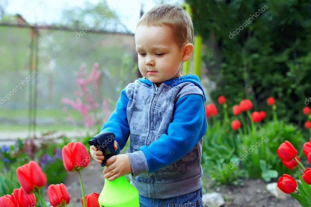 Cute Baby Boy Irrigating Flowers In Colorful Garden Stock Photo