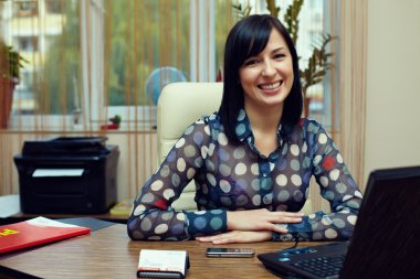 attractive friendly woman sitting in workplace. office interior