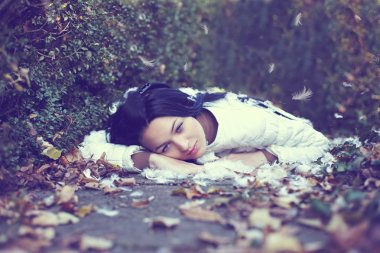 Mystic lonely angel girl lying on the ground among the fallen leaves and fe