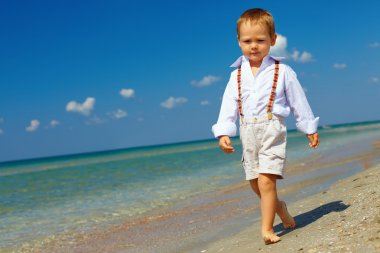 Confident baby boy goes forward in firm gait, sea beach