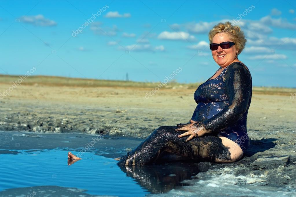 Smiling mature plump woman taking mud treatment on summer day — Stock Photo