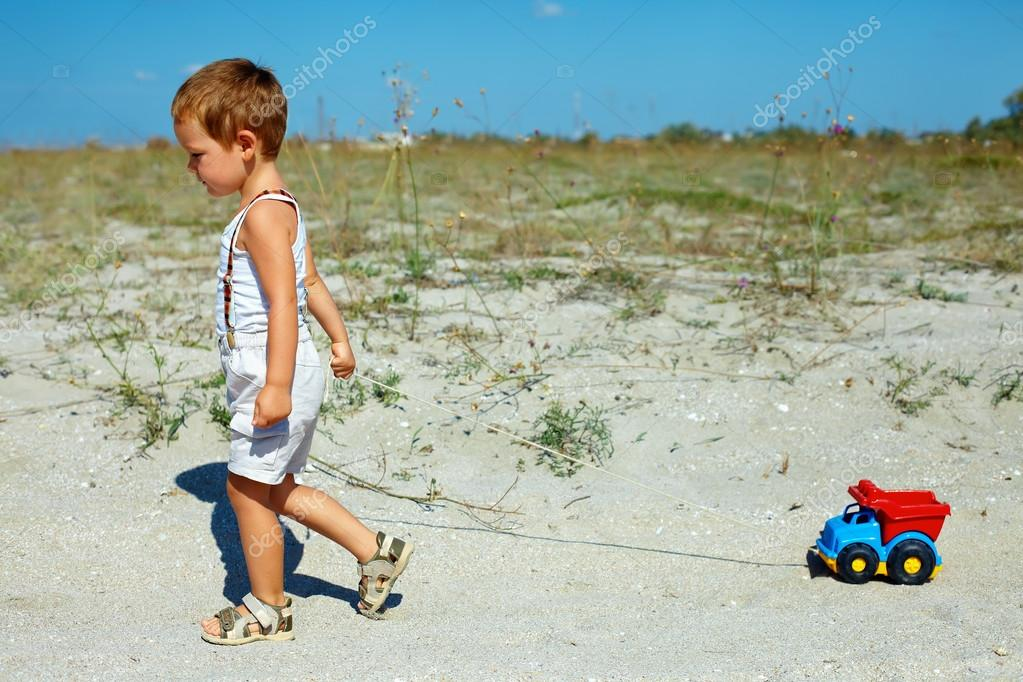Cute baby boy dragging toy car walking at the field