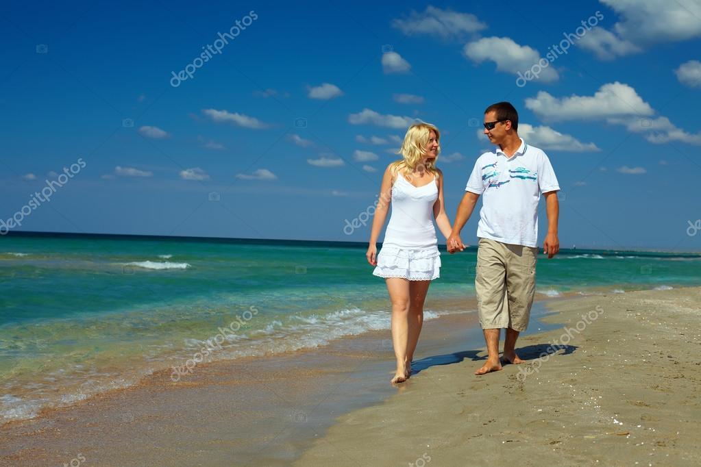 Holiday romance, happy couple walking on beach
