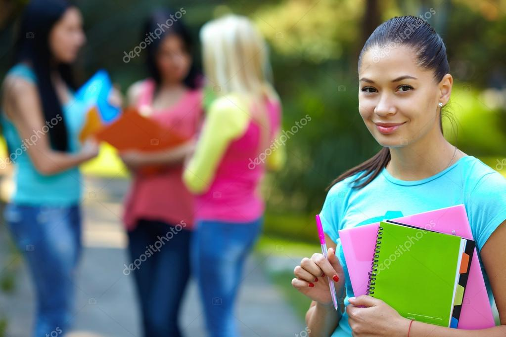 Pretty student outdoors with a group of on the background