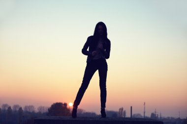 Silhouette of slim seductive woman standing on rooftop at sunset. urban ba