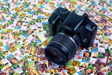 Photo business. SLR camera lying on huge number of digital prin