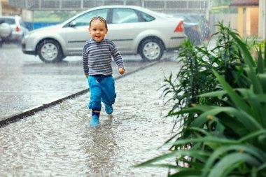Cute baby boy running under the driving rain