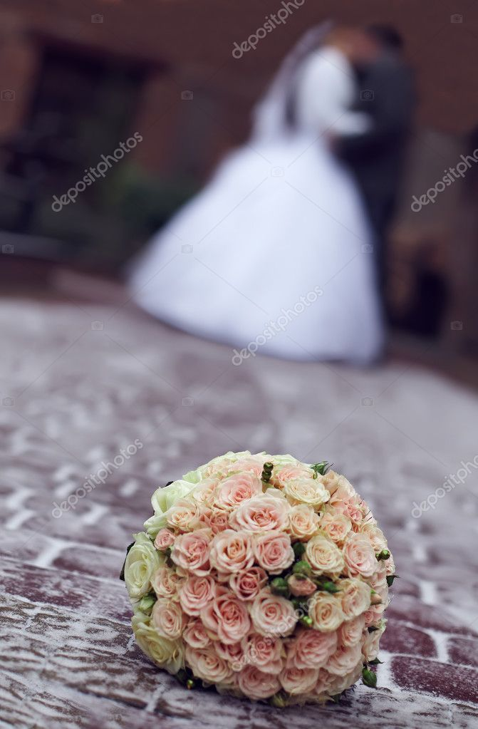 Outdoor winter close-up of wedding bouquet lying on snow on a bride and gro