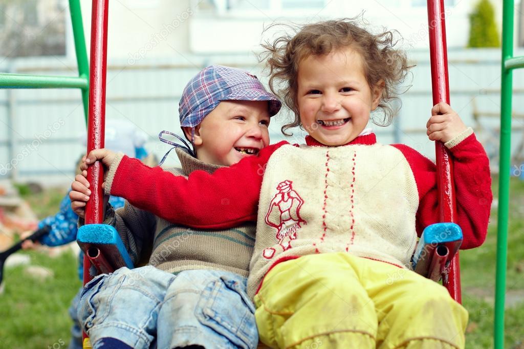 Dirty, happy little gypsy siblings on swings outdoor