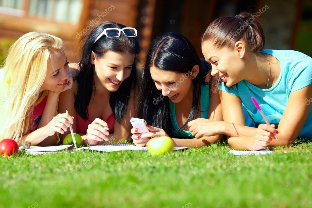 Group of happy college girls chatting in social network on green lawn